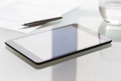 在现代玻璃桌上的数字式片剂在办公室 库存照片