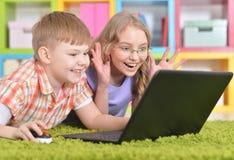 在现代膝上型计算机前面的少年 图库摄影