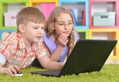 在现代膝上型计算机前面的少年 库存照片