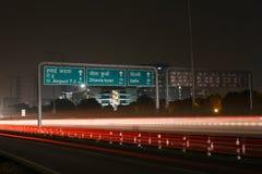 在现代道路基础设施的高速车在古尔冈,德里,印度 在晚上被射击的艺术性的长的曝光 库存图片