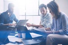 在现代coworking的演播室的小组三个年轻工友 指向在纸张文件和谈话的妇女 免版税库存照片