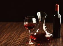 在玻璃、蒸馏瓶和瓶的红葡萄酒在桌上 免版税图库摄影
