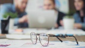 在玻璃下的财政图和企业同事开会议在背景 影视素材