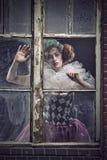 在玻璃之后的一名pierrot妇女 库存图片