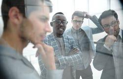 在玻璃之后 企业队认为一个新的项目的想法 免版税库存图片