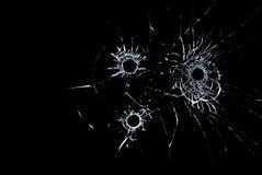在玻璃关闭的三个弹孔在黑背景 库存照片