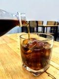 在玻璃冰的可乐,从玻璃瓶的倾吐的可乐在休息喝对与冰块的一块玻璃,在玻璃冰饮料的可乐喝 免版税库存图片