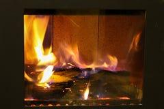 在玻璃后的火在一个闭合的壁炉 库存图片