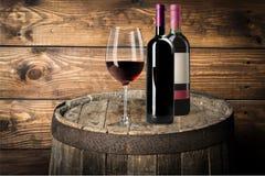 在玻璃和瓶的红葡萄酒在木桶 免版税库存图片