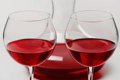 在玻璃和蒸馏瓶的红葡萄酒在背景 图库摄影