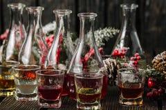 在玻璃和蒸馏瓶的被分类的酒精甘露酒有圣诞节装饰的 免版税库存照片