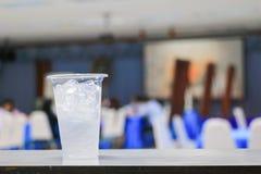 在玻璃塑料的冰水在研讨会会议室背景中 选择与浅景深的焦点 免版税图库摄影
