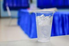 在玻璃塑料的冰水在研讨会会议室背景中 选择与浅景深的焦点 库存图片