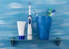 在玻璃是机械牙刷,下电和牙膏,在蓝色背景 免版税库存照片