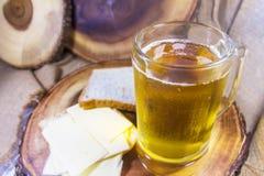 在玻璃杯子和关闭的啤酒乳酪用在木背景的面包 库存图片
