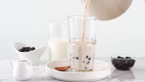 在玻璃杯子的倾吐的奶茶有在明亮的大理石桌和白色盘子,自创conce上的鲜美普遍的台湾珍珠粉珍珠泡影的 影视素材