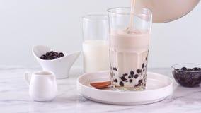 在玻璃杯子的倾吐的奶茶有在明亮的大理石桌和白色盘子,自创conce上的鲜美普遍的台湾珍珠粉珍珠泡影的 股票录像