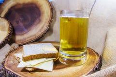 在玻璃杯子的啤酒吃用乳酪和面包在木板材被安置了作为背景 免版税库存照片
