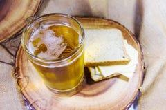 在玻璃杯子的啤酒用乳酪和面包投入了木板材作为背景 免版税库存图片