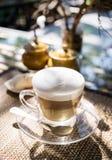 在玻璃杯子的层状热奶咖啡在泰国咖啡馆的桌上在室外温暖的阳光下 被弄脏的自然在背景中 汽车城市概念都伯林映射小的旅行 图库摄影