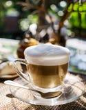 在玻璃杯子的层状热奶咖啡在泰国咖啡馆的桌上在室外温暖的阳光下 被弄脏的自然在背景中 汽车城市概念都伯林映射小的旅行 免版税库存照片