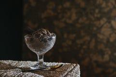 在玻璃杯子的巧克力沫丝淋在柳条桌上 库存照片