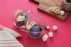 在玻璃杯子的法国macarons有花和糖的在桃红色背景 木书桌用曲奇饼 正面图 免版税库存图片