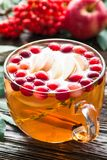 在玻璃杯子的热的苹果蔓越桔桂香茶在木桌上 库存图片