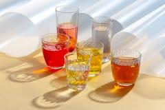 在玻璃杯子的色的饮料在与附加要素的黄色背景 库存图片