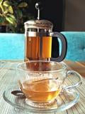 在玻璃杯子的茶在与水壶的木桌上 免版税库存图片