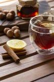 在玻璃杯子的茶用在木背景的柠檬和香草荚 榛子和果酱在瓶子在后边木委员会 库存图片