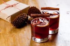 在玻璃杯子的被仔细考虑的酒用香料 在木桌上的圣诞节热的饮料与工艺礼物 库存照片