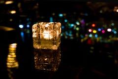在玻璃杯子的Blurred灼烧的蜡烛有香港海岛夜视图 库存图片