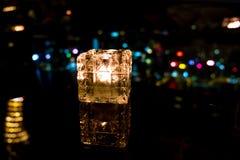 在玻璃杯子的Blurred灼烧的蜡烛有香港海岛夜视图 图库摄影