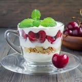 在玻璃杯子,樱桃verrine,方形的格式的樱桃、muesli和酸奶点心 免版税库存照片