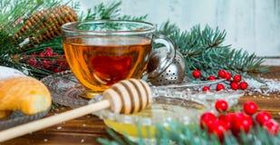 在玻璃杯的圣诞节茶 构成用曲奇饼,杉木分支,在诗歌选背景的锥体在木桌上的 库存照片