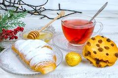 在玻璃杯的圣诞节茶 构成用曲奇饼,杉木分支,在诗歌选背景的锥体在木桌上的 库存图片