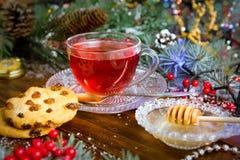 在玻璃杯的圣诞节茶 构成用曲奇饼,杉木分支,在诗歌选背景的锥体在木桌上的 图库摄影