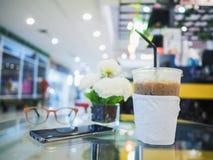 在玻璃桌上的冰冻咖啡弄脏了咖啡馆背景 库存图片