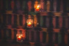 在玻璃烛台的蜡烛照亮在葡萄酒样式的五颜六色的墙壁 免版税库存图片