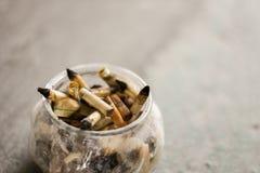 在玻璃烟灰缸的熏制的烟头有灰色背景 免版税库存图片
