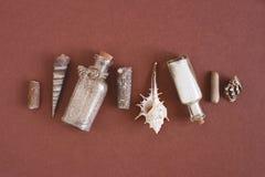 在玻璃瓶、海壳和石头的沙子 库存照片