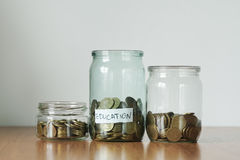 在玻璃瓶子不同的需要的,钱箱的硬币 现金储款概念的发行 educationsticker 免版税库存图片