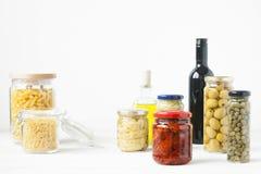 在玻璃瓶子保存的典型的意大利食物品种  免版税库存照片
