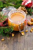 在玻璃瓶子和圣诞节装饰的自创盐味的焦糖调味汁在木背景 图库摄影