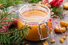 在玻璃瓶子和圣诞节装饰的自创盐味的焦糖调味汁在木背景 免版税图库摄影
