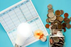 在玻璃瓶子和外部,与发光的泰国货币金钱的硬币 免版税库存图片