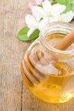 在玻璃瓶子和棍子的蜂蜜 图库摄影