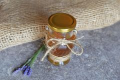 在玻璃瓶子和淡紫色花的蜂蜜 库存照片