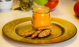 在玻璃瓶子和灰浆的五颜六色的印度香料姜黄和豆蔻果实香料的关闭  免版税库存照片